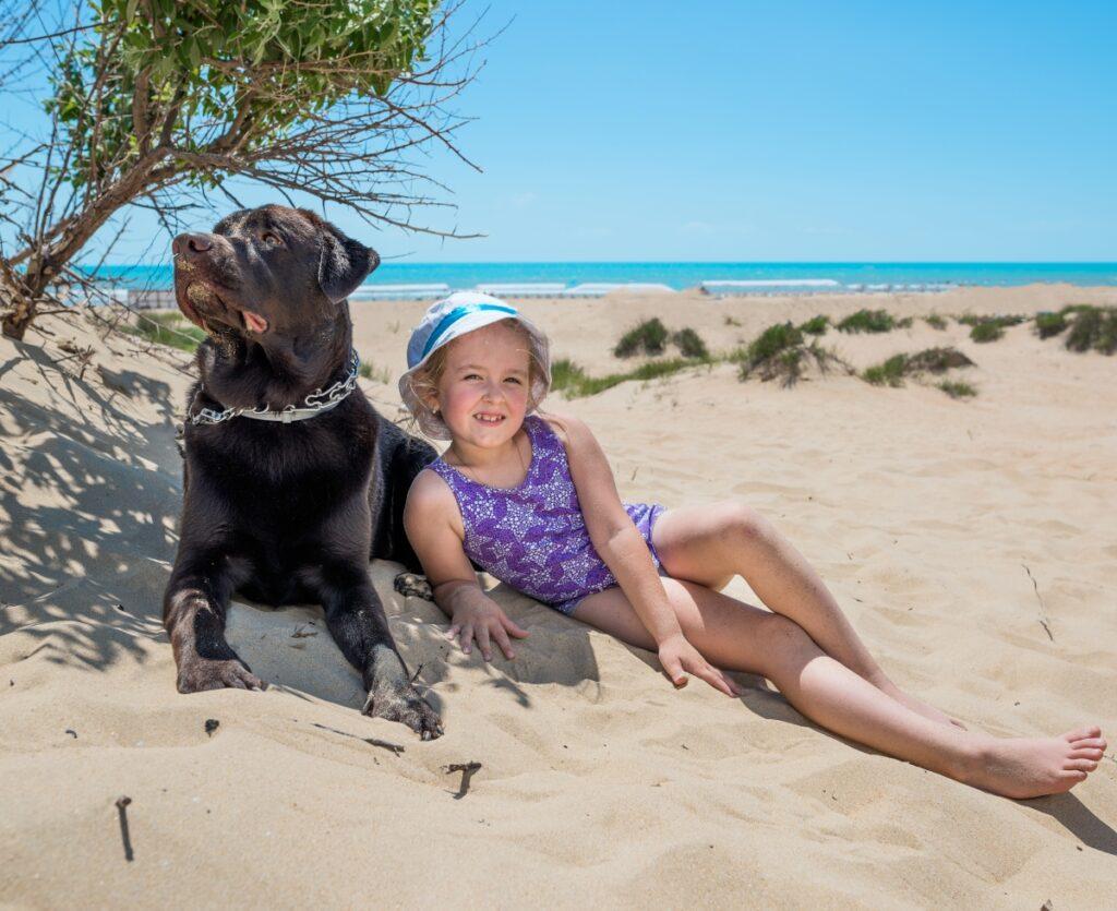 devojcica i pas na plazi